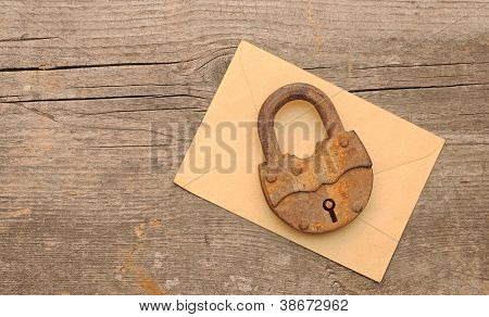 Old padlock on yellow envelope over  wooden background. With copy space