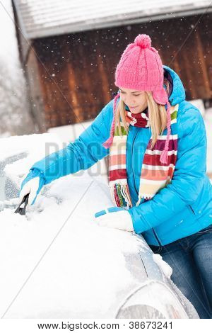Woman cleaning snow car hood with scraper winter wiping young