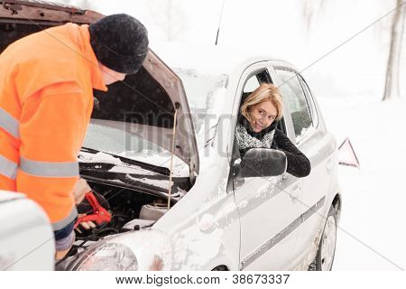 Man repairing woman's car snow assistance winter broken tools mechanic