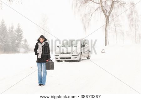Woman walking with gas can snow car road winter trouble
