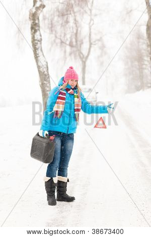 Woman hitchhiking on road snow gas can car breakdown problem
