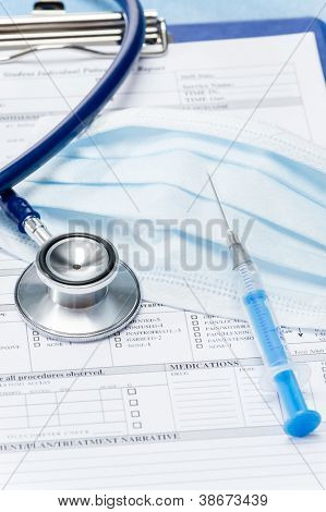 Stethoscope with injection protective mask lying over medical chart