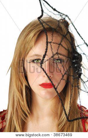 Mooie vrouw gekleed als een heks met spinrag in het haar