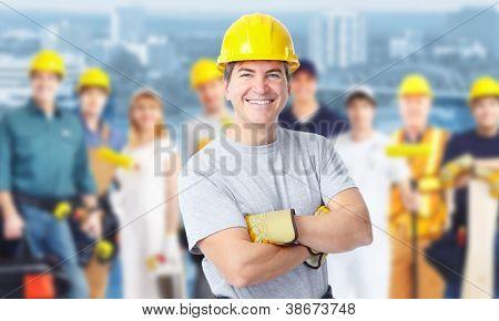 Sonriente hombre trabajador de construcción. Antecedentes de la arquitectura.