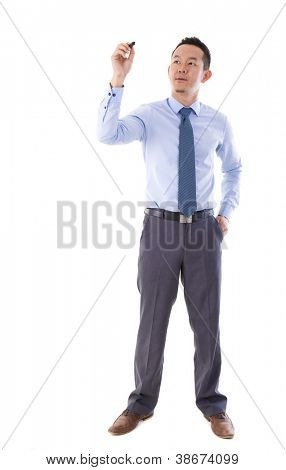 Mid aged Asian male in blue shirt writing something on glass board with marker