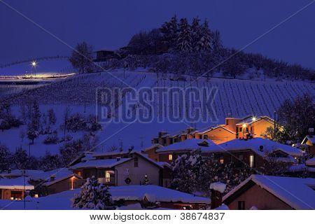 Ver en Cerro Nevado con casas en la noche en la ciudad de Alba en Piamonte, norte de Italia.