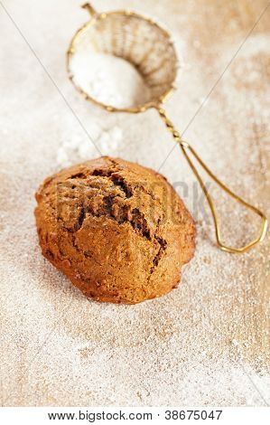 soft ginger cookie on wooden table, sieve with caster sugar on background, shallow dof