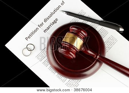 Divorce decree and wooden gavel on black background