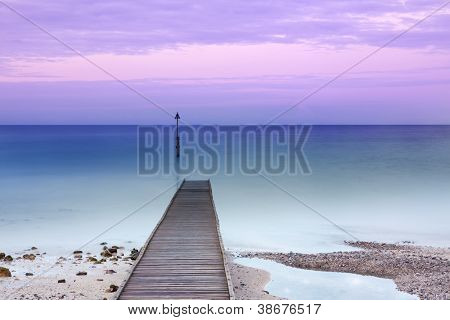 Wooden jetty partially under water, long exposure at dusk