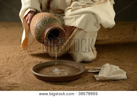 Jesus with a jug of water and a towel on a neutral background