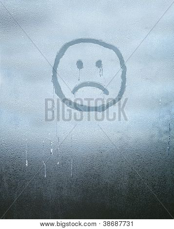 Sad face drawn over condensed glass