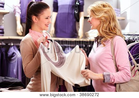 Image of two pretty girls choosing clothes from new collection in department store