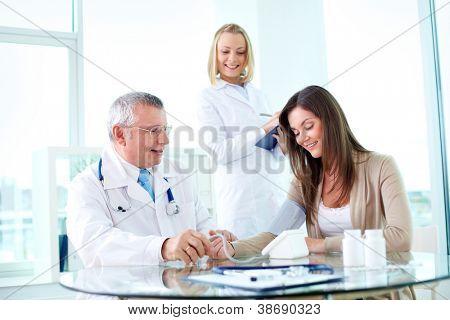 Porträt eines männlichen Praktizierenden, die Messung des Blutdrucks Patienten mit Krankenschwester in der Nähe von