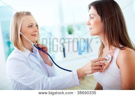 Portrait of confident practitioner checking heart beat of patient
