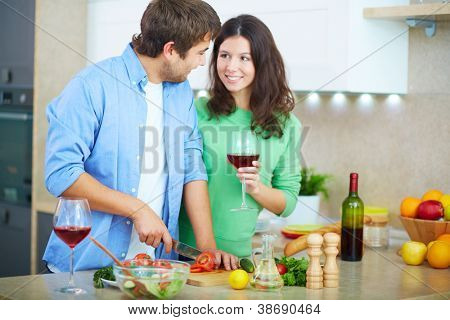 Portrait of young man cooking salad and looking at his wife with glass of red wine in the kitchen