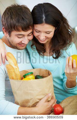 Casal jovem procurando no paperbag com produtos com sorrisos