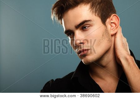 Trendy young man in black shirt, portrait of sexy fashion boy looking right over dark blue
