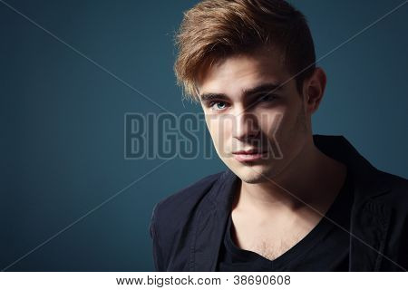 Handsome trendy young man in black shirt, portrait of sexy fashion guy over dark blue background