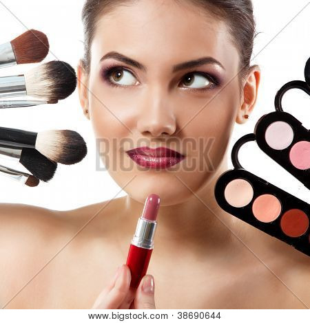 beauty portrait of young beautiful woman with makeup brushes, lipstick and palette of eye shadows isolated on white background