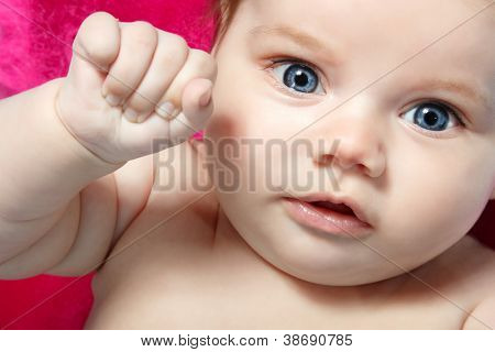 cute baby with wide opened blue eyes, beautiful kid's face and hands closeup, studio shot