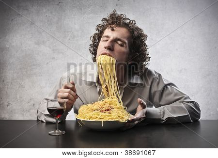 Man gorging of spaghetti and drinking wine