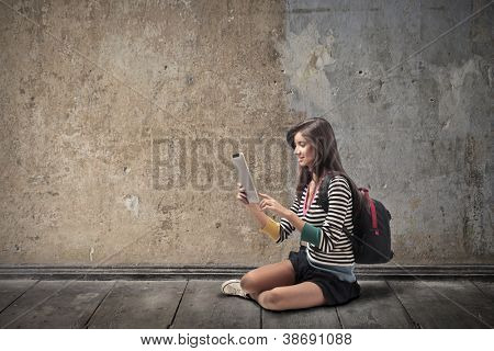 Beautiful brown girl, with a backpack, on the street, using a tablet pc