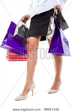 Attractive female in high heels with shopping bags over white