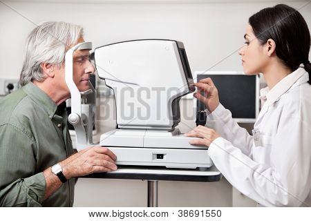 Young optometrist performing visual field test with an advance equipment