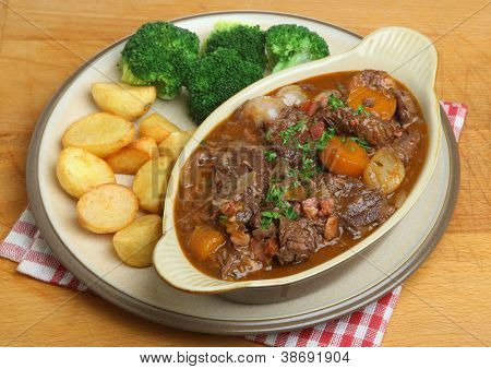 Beef bourguignon stew dinner served with roast potatoes and broccoli.