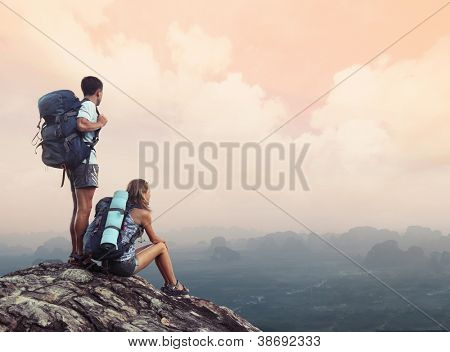 Two hikers with backpacks standing on top of a mountain and enjoying a valley view