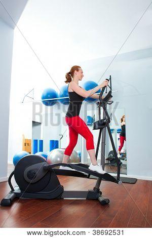 Aerobics cardio training woman on elliptic crosstrainer bicycle at gym