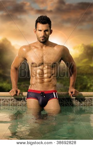 Sexy male model with great body and abs in pool