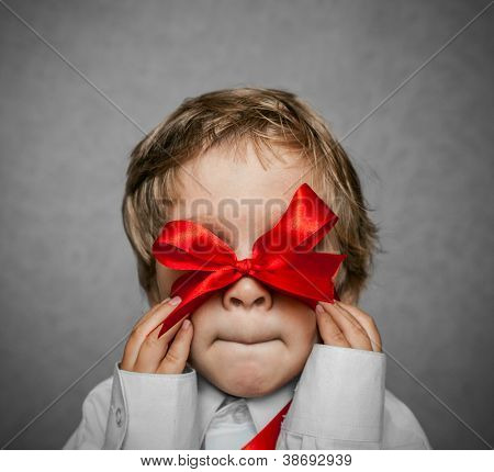 little boy with a red bow in hand