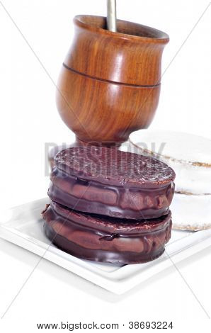 a plate with argentinean-uruguayan alfajores and a mate infusion in a mate recipient on a white background