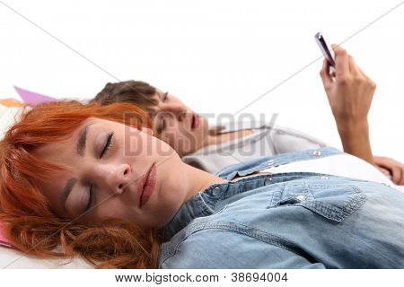 two teenage girls relaxing on the bed