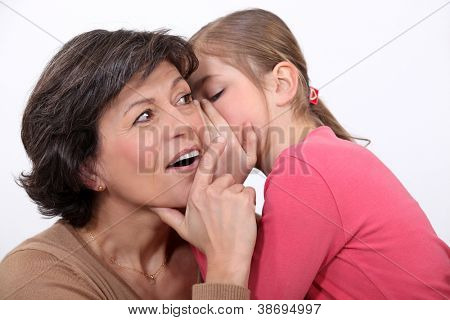A little girl telling her mother a secret.