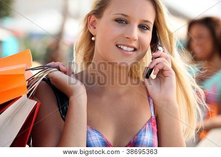 Young woman talking on her mobile phone while shopping