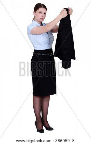 Unhappy businesswoman hanging her blazer up