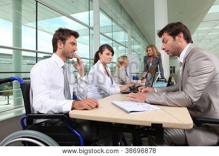 Man in rolstoel werken in een kantoor