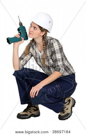 Handywoman crouching with drill