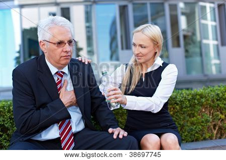 Woman offering exhausted senior business man a bottle of water