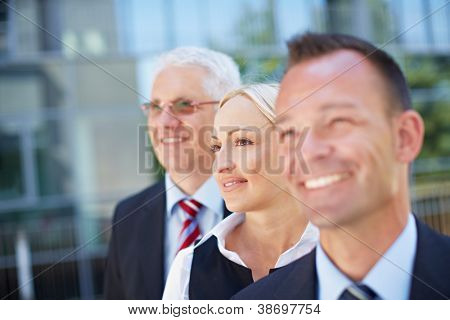 Visionary business team in a row looking into the same direction outside