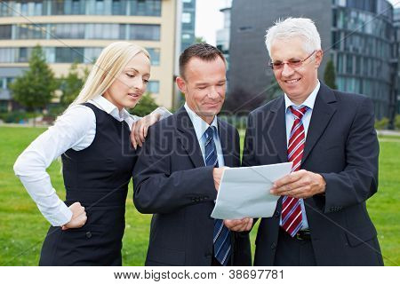 Three business people outside the office reading a contract