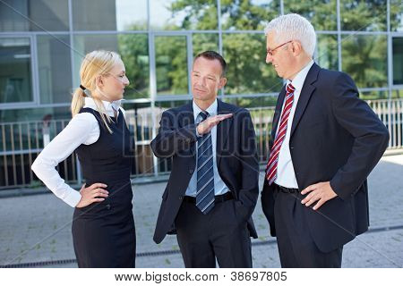 Two business people listening to the speech of a manager