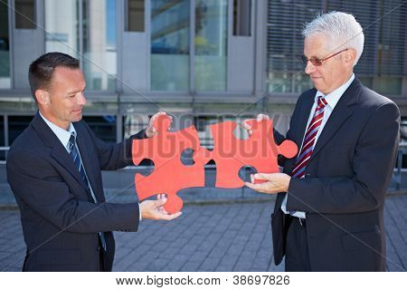 Business people solving a problem symbolized with two red jigsaw puzzle pieces