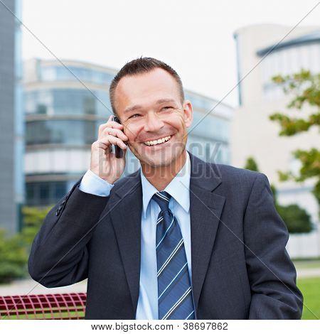Happy business man making a call with his smartphone outside