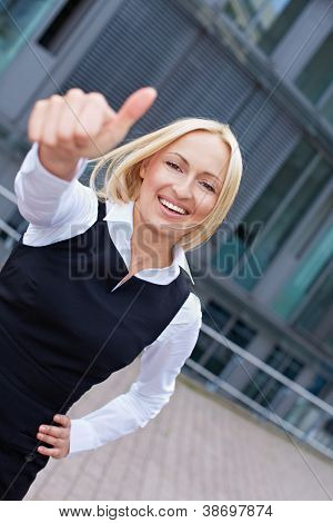 Attractive business woman in the city holding her thumbs up