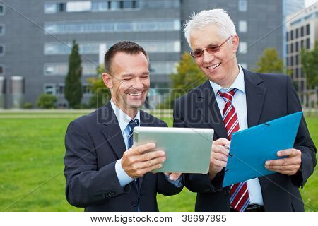 Two business people outside looking at a tablet computer