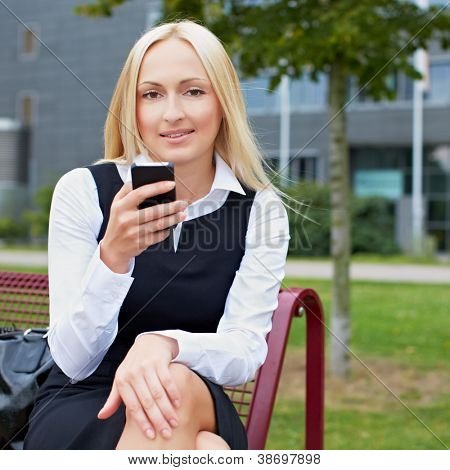 Attractive business woman using smartphone in a park