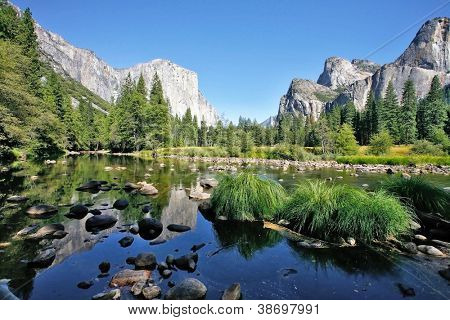 The magnificent Yosemite Valley. The huge granite monolith El Capitan and the blue sky reflected in the smooth waters of the river Mersed